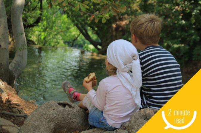 Children sitting watching river