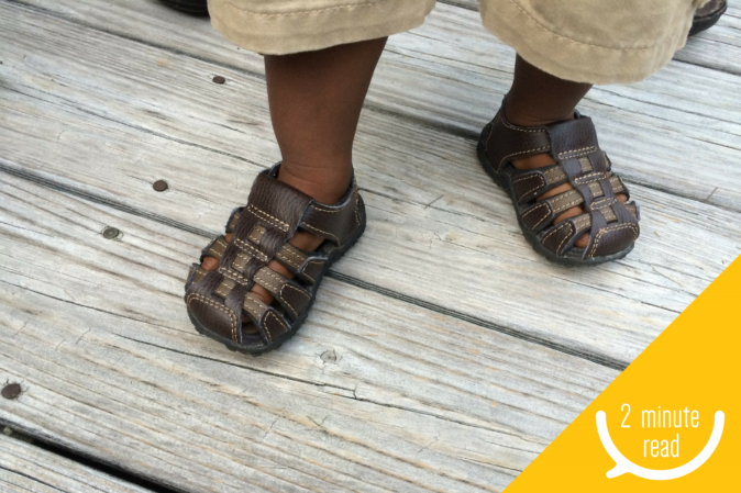 Child with sandals standing on deck