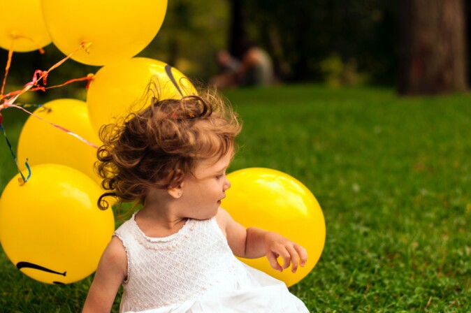 Toddler playing with balloons